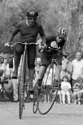 Two cyclists competing with each other in a Penny Farthing race
