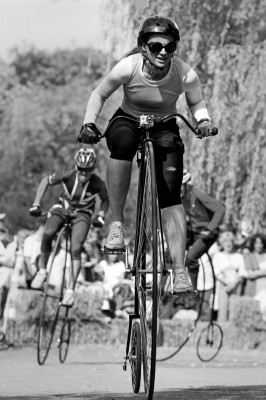 lady cyclist racing a penny farthing bicycle